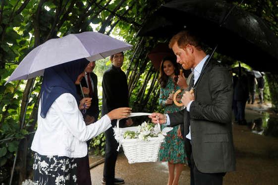 Slide 3 de 20: Príncipe Harry (à direita) recebe flores durante evento no jardim memorial no Palácio de Kensington