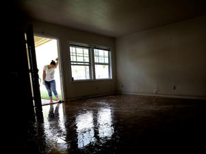 Alejandro Castillo takes a break from carrying water-soaked items out of her family's home after flood waters receded Thursday, Aug. 31, 2017, in Houston. The city continues to recover from record flooding caused by Harvey.