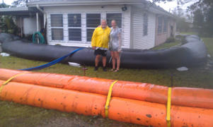 The Rogers family, posing in front of the 30-inch tall AquaDam protecting their home in Lafitte, Louisiana.