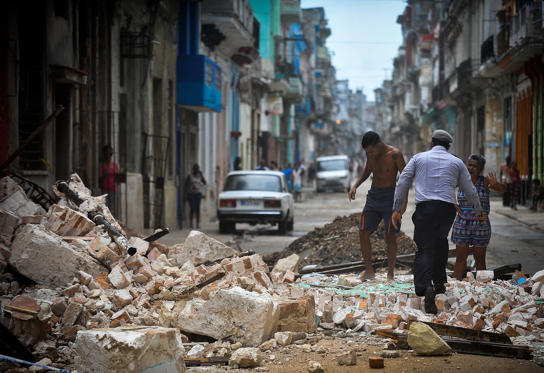 Slide 1 of 73: Cubans wade through the rubble from a collapsed building in Havana, on September 9, 2017.  Irma's blast through the Cuban coastline weakened the storm to a Category Three, but it is still packing 125 mile-an-hour winds (205 kilometer per hour) and was expected to regain power before hitting the Florida Keys early Sunday, US forecasters said. The Cuban government extended its maximum state of alert to three additional provinces, including Havana, amid fears of flooding in low-lying areas. / AFP PHOTO / YAMIL LAGE        (Photo credit should read YAMIL LAGE/AFP/Getty Images)