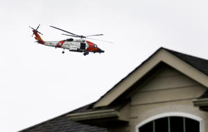 A US Coast Guard helicopter flies over Autumn Lake, a subdivision in Pearland, Texas, looking for flood victims on August 29, 2017.