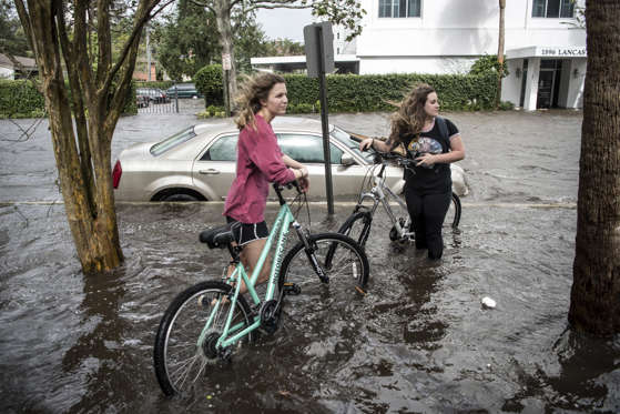 Slide 9 of 127: Two young women explore storm surge flood waters from Hurricane Irma along the St. Johns River at Memorial Park on Sept. 11, 2017 in Jacksonville, Florida. Flooding in downtown Jacksonville along the river topped a record set during Hurricane Dora in 1965.