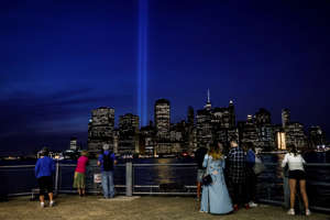 People watch the Tribute in Light installation illuminated over lower Manhattan as seen from Brooklyn, marking the 16th anniversary of the 9/11 attacks in New York City, U.S., September 11, 2017. REUTERS/Brendan McDermid     TPX IMAGES OF THE DAY - RC169CC05F80