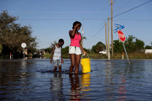Nineve Desronvil, 20, left, and her brother Jeffrey 8, wade through their flooded street trying to catch fish in the aftermath of Hurricane Irma in Fort Myers, Fla., Wednesday, Sept. 13, 2017.