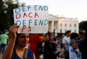 "A woman holds up a sign that reads ""Defend DACA Defend TPS"" during a rally supporting Deferred Action for Childhood Arrivals, or DACA, outside the White House in Washington, Monday, Sept. 4, 2017."