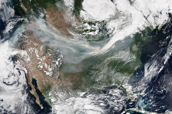 """Slide 1 of 27: With dozens of wildfires burning across the western United States and Canada, many North Americans have had the acrid taste of smoke in their mouths during the past few weeks. On September 5, 2017, the National Interagency Fire Center (NIFC) reported more than 80 large fires burning in nine western U.S. states. People living in large stretches of northern California, Oregon, Washington, and Idaho have been breathing what the U.S. government's Air Now website rated as """"hazardous"""" air. The natural-color mosaic above was made from several scenes acquired on September 4, 2017, by the Visible Infrared Imaging Radiometer Suite (VIIRS) on the Suomi National Polar-orbiting Partnership (Suomi-NPP) satellite. The Ozone Mapper Profiler Suite (OMPS) on Suomi NPP also collected data on airborne aerosols as they were swept by winds from west to east across the continental United States (second image). The OMPS map depicts relative aerosol concentrations, with lower concentrations appearing in yellow and higher concentrations appearing in dark orange-brown. Note that the sensor detects aerosols in high-altitude plumes more readily than lower plumes, so this map does not reflect air quality conditions at """"nose height."""" Rather it shows where large plumes of smoke were lofted several kilometers up into the atmosphere. On September 5, roughly 7.8 million acres had burned in the United States since the beginning of 2017, according to NIFC. """"While it is unlikely that this season will be record-breaking for modern fire record keeping in the western United States, it is above normal relative to the last decade—which has seen abundant fire activity,"""" said John Abatzoglou, a fire researcher at the University of Idaho. Unusually warm and dry conditions across a broad swath of the West has fueled the active fire season, noted Abatzoglou. A wet winter in some parts of the West also contributed by triggering the growth of more grass in the spring—grass that turns into fuel for fi"""