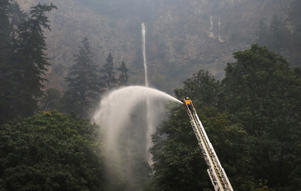 A firefighter maintains a spray of water on the trees around Multnomah Falls Wednesday Sept. 6, 2017, as the Eagle Creek Fire continues to burn east of Troutdale, Ore.