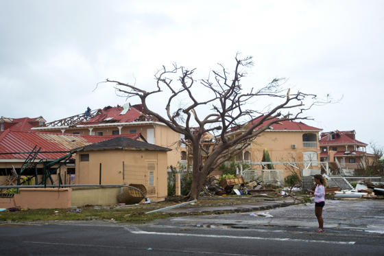 Slide 2 of 51: TOPSHOT - A woman stands near damaged homes in Marigot, near the Bay of Nettle, on the French Collectivity of Saint Martin, on September 6, 2017, after the passage of Hurricane Irma. France, the Netherlands and Britain on September 7 sent water, emergency rations and rescue teams to their stricken territories in the Caribbean hit by Hurricane Irma, which has killed at least 10 people. The worst-affected island so far is Saint Martin, which is divided between the Netherlands and France, where eight of the 10 confirmed deaths took place.  / AFP PHOTO / Lionel CHAMOISEAU        (Photo credit should read LIONEL CHAMOISEAU/AFP/Getty Images)