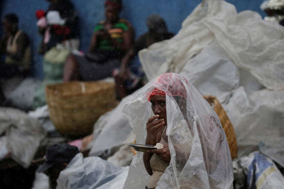 Slide 1 of 51: A woman protects herself from rain brought by Hurricane Irma as she eats lunch in a street of Cap-Haitien, Haiti, September 7, 2017