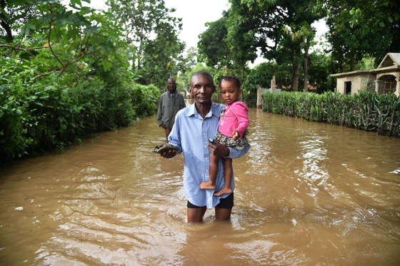 Slide 3 of 55: A man walks in street that was flooded in Malfeti, in the city of Fort Liberte, in the city of Fort Liverte, in the north east of Haiti, on September 8, 2017, during the passage of Hurricane Irma. Irma has been downgraded to a Category Four hurricane but is still extremely dangerous, the National Hurricane Center said. / AFP PHOTO / HECTOR RETAMAL (Photo credit should read HECTOR RETAMAL/AFP/Getty Images)