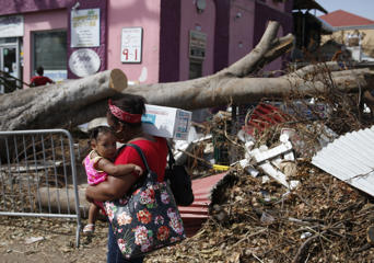 A woman passes debris from Hurricane Irma strewn in Cruz Bay on St. John in the US Virgin Islands on Sept. 12, 2017. The island was hit hard by Hurricane Irma.