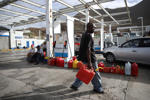 A man carries containers to fill with gas at a gas station following Hurricane Irma in Cole Bay, Sint Maarten (Saint Martin) island, Netherlands, September 16, 2017. REUTERS/Andres Martinez Casares - RC1C7DA50500