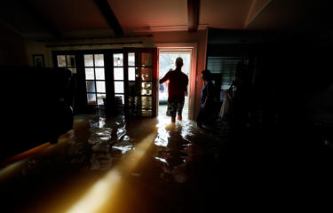 A family that wanted to remain anonymous moves belongings from their home flooded by Harvey in Houston, Texas August 31, 2017.