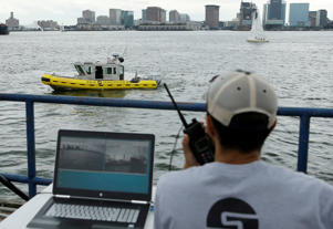 Computer scientist Mohamed Saad Ibn Seddik, of Sea Machines Robotics, uses a laptop to guide a boat outfitted with sensors and self-navigating software and capable of autonomous navigation in Boston Harbor.
