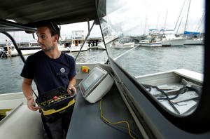 Frank Marino, an engineer with Sea Machines Robotics, uses a remote control belt pack to control a self-driving boat in Boston Harbor.