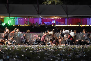 People dive for cover at Route 91 Harvest country music festival after apparent gun fire was heard on October 1, 2017 in Las Vegas, Nevada.