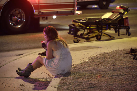 Slide 2 of 16: A woman sits on a curb at the scene of a shooting outside of a music festival along the Las Vegas Strip, Monday, Oct. 2, 2017, in Las Vegas. Multiple victims were being transported to hospitals after a shooting late Sunday at a music festival on the Las Vegas Strip.
