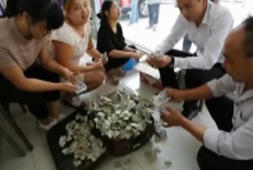 Couple buy car with bag of origami hearts made out of banknotes