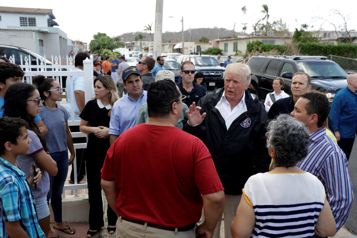 CAPTION: President Donald Trump and Puerto Rico Governor Ricardo Rosselló, center, listen to residents and survey hurricane damage and recovery efforts in a neighborhood in Guaynabo, Puerto Rico, Tuesday, Oct. 3, 2017.