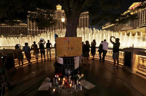 People take photos of the fountain at the Bellagio hotel in front of a memorial for victims of the mass shooting in Las Vegas, Tuesday, Oct. 3, 2017.