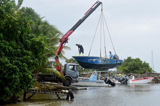 Slide 82 of 82: Men remove boats from the water ahead of Hurricane Maria in the Galbas area of Sainte-Anne on the French Caribbean island of Guadeloupe, early Monday, Sept. 18, 2017.