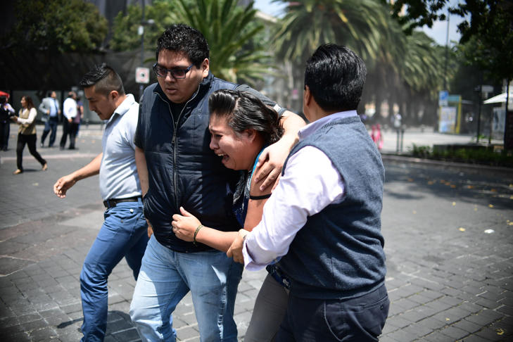 People react after a strong earthquake strikes in Mexico City on Tuesday. The city was holding preparation earthquake drills on the anniversary of a 1985 temblor.