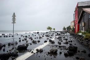 "A picture shows rocks swept by strong waves onto a road in Le Carbet, on the French Caribbean island of Martinique, after it was hit by Hurricane Maria, on September 19, 2017. Hurricane Maria headed towards the Virgin Islands and Puerto Rico on September 19, with the US National Hurricane Center warning of a ""potentially catastrophic"" impact as it battered the eastern Caribbean. Arriving just as islanders in the region are struggling to recover from devastating Hurricane Irma which struck earlier this month, Maria claimed its first victim in the French territory of Guadeloupe, where two other people were missing."