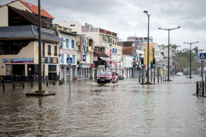 A motorist drives on the flooded waterfront in Fort-de-France, on the French Car...