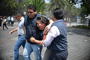 People react as a real quake rattles Mexico City on September 19, 2017 moments after an earthquake drill was held in the capital. A powerful earthquake shook Mexico City on Tuesday, causing panic among the megalopolis' 20 million inhabitants on the 32nd anniversary of a devastating 1985 quake. The US Geological Survey put the quake's magnitude at 7.1 while Mexico's Seismological Institute said it measured 6.8 on its scale.