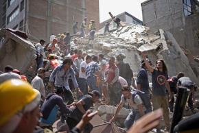 People remove debris from a collapsed building following an earthquake in the ne...
