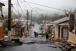 Rescue workers help people after the area was hit by Hurricane Maria in Guayama,...