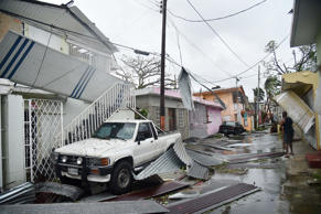 Residents of San Juan, Puerto Rico, deal with damages to their homes on Septembe...