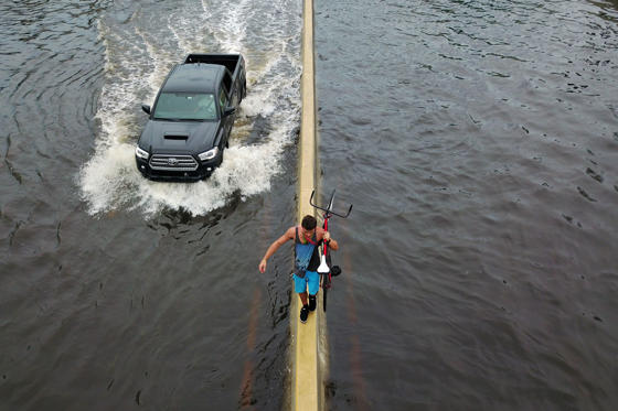 "TOPSHOT - A man walks on a highway divider while carrying his bicycle in the aftermath of Hurricane Maria in San Juan, Puerto Rico, Thursday, September 21, 2017. Puerto Rico braced for potentially calamitous flash flooding after being pummeled by Hurricane Maria which devastated the island and knocked out the entire electricity grid. The hurricane, which Puerto Rico Governor Ricardo Rossello called ""the most devastating storm in a century,"" had battered the island of 3.4 million people after roaring ashore early Wednesday with deadly winds and heavy rain.  / AFP PHOTO / Ricardo ARDUENGO        (Photo credit should read RICARDO ARDUENGO/AFP/Getty Images)"