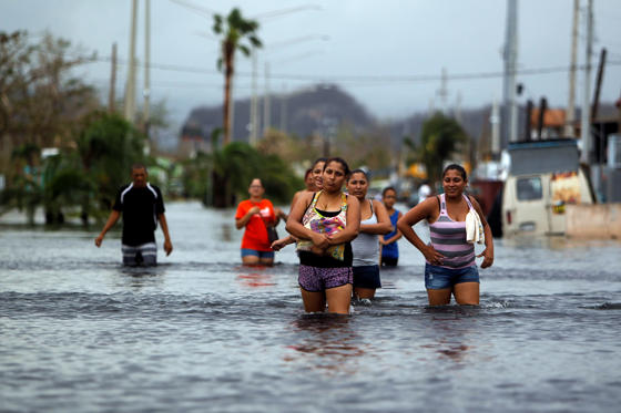 Slide 2 of 82: People walk on a flooded street in the aftermath of Hurricane Maria in San Juan, Puerto Rico on September 22, 2017. Puerto Rico battled dangerous floods Friday after Hurricane Maria ravaged the island, as rescuers raced against time to reach residents trapped in their homes and the death toll climbed to 33. Puerto Rico Governor Ricardo Rossello called Maria the most devastating storm in a century after it destroyed the US territory's electricity and telecommunications infrastructure.
