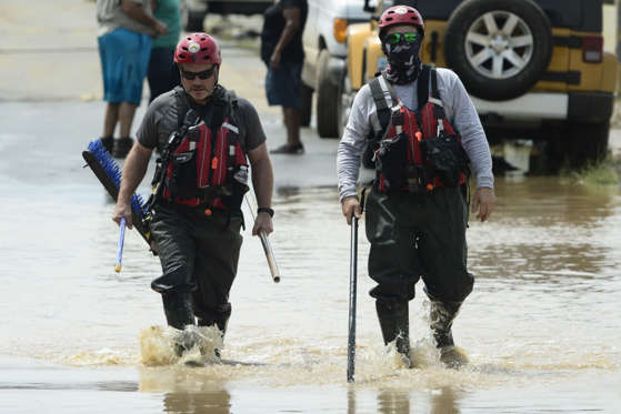 Slide 3 of 82: Personnel from a FEMA search and rescue crew walk in a flooded road, after the passing of Hurricane Maria, in Toa Baja, Puerto Rico, Friday, September 22, 2017. Because of the heavy rains brought by Maria, thousands of people were evacuated from Toa Baja after the municipal government opened the gates of the Rio La Plata Dam.