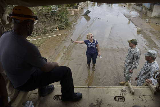 Slide 1 of 82: National Guard personnel offer evacuation to a Toa Ville resident after the passing of Hurricane Maria, in Puerto Rico, Friday, September 22, 2017. Because of the heavy rains brought by Maria, thousands of people were evacuated from Toa Baja after the municipal government opened the gates of the Rio La Plata Dam.