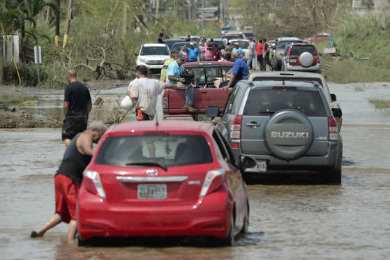 Slide 4 of 82: Residents drive through a flooded road after the passing of Hurricane Maria, in Toa Baja, Puerto Rico, Friday, September 22, 2017. Because of the heavy rains brought by Maria, thousands of people were evacuated from Toa Baja after the municipal government opened the gates of the Rio La Plata Dam.