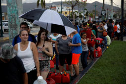 People queue to buy gasoline after the area was hit by Hurricane Maria in Caguas, Puerto Rico on September 22, 2017.