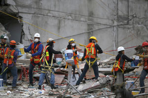 Search and rescue workers remove rubble a bucket at a time while standing on the debris of a felled office building brought down by a 7.1-magnitude earthquake, in the Roma Norte neighborhood of Mexico City, Sunday, Sept. 24, 2017. As rescue operations stretched into day 6, residents throughout the capital have held out hope that dozens still missing might be found alive.