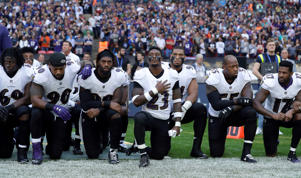 Baltimore Ravens players kneel down during the playing of the U.S. national anthem before an NFL football game against the Jacksonville Jaguars at Wembley Stadium in London, Sunday Sept. 24, 2017.