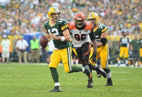 Aaron Rodgers #12 of the Green Bay Packers rolls out looking to pass during the ...
