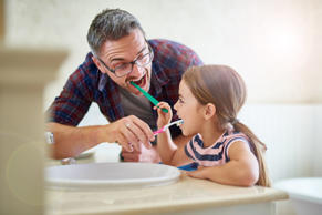 Shot of a father and his daughter brushing their teeth