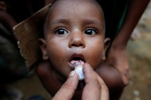 A Rohingya refugee child gets an oral cholera vaccine, distributed by the World Health Organisation (WHO) with the help of volunteers and local NGO's, in a refugee camp near Cox's Bazar, Bangladesh Oct. 11, 2017.