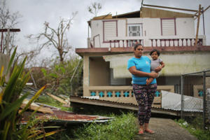 Yamiles Vazquez poses with her baby Joy on a section of her family's damaged property three weeks after Hurricane Maria hit the island, on October 11, 2017 in Aibonito, Puerto Rico.