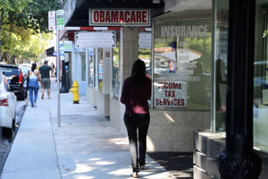 "A woman walks past a sign advertising ""Obamacare"", Tuesday, Jan. 31, 2017, in Miami."