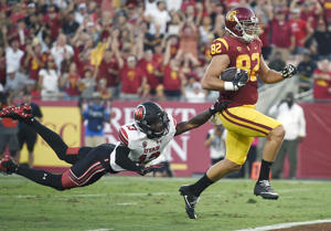 Southern California tight end Tyler Petite, right, runs in the ball after a catch for a touchdown ahead of Utah defensive back Marquise Blair during the first half of an NCAA college football game in Los Angeles, Saturday, Oct. 14, 2017.