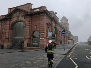 A firefighter close to Nottingham railway station which has been evacuated and services passing through cancelled after a fire broke out.