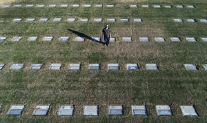Darin Roam stands among headstones at the Selma cemetery, where he has been cleaning headstones and edging the grass around them, on Wednesday, Dec. 6, 2017. Roam has been spending up to eight hours a day cleaning headstones at the cemetery. (Craig Kohlruss/Fresno Bee/TNS)