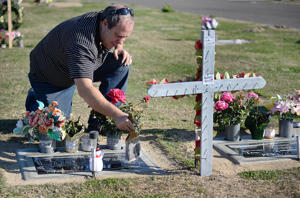 Darin Roam uses a paint brush to clean the head stones of his late wife and father at the Selma cemetery on Wednesday, Dec. 6, 2017. (Craig Kohlruss/Fresno Bee/TNS)