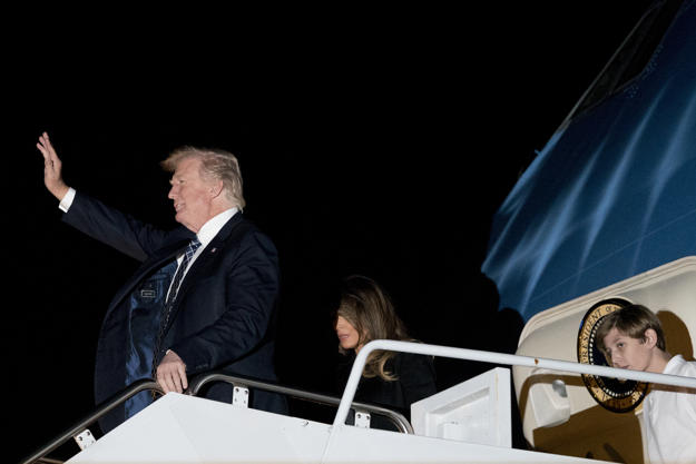 President Donald Trump, accompanied by first lady Melania Trump, center, and their son Barron Trump, right, arrives at Palm Beach International Airport in West Palm Beach, Fla., Friday, Jan. 12, 2018.